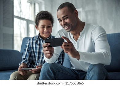 Happy Afro American father and son in casual clothes are using gadgets and smiling while sitting on couch at home