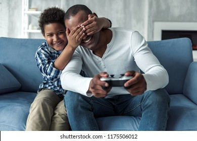 Happy Afro American father and son on couch at home, boy is covering his dad's eyes and smiling while dad is playing video game console