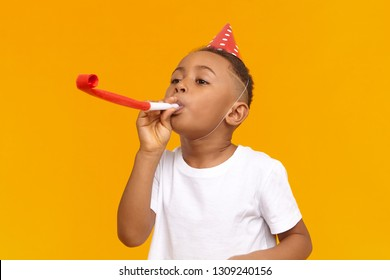 Happy Afro American little boy celebrating his ten year birthday with friends, posing isolated at blank yellow wall, blowing whistle, holiday hat on his head. Fun, joy, celebration and holiday
