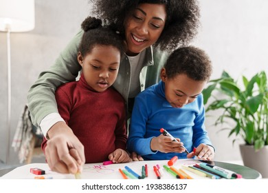 Happy afro american mother smiling while drawing with her children at home