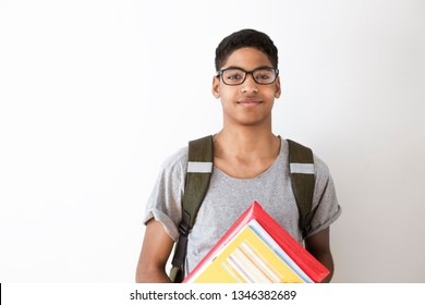 Happy afro american student in glasses with books. Portrait of a black young man with textbooks in his hands. Smiling boy with a backpack and notebooks on a white background. The concept of education.