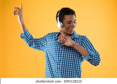Happy Afro American teenager in headphones listens to music. Isolated on yellow background. Studio portrait.