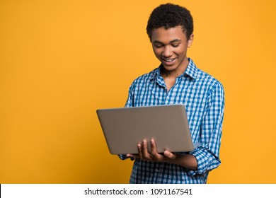 Happy Afro American teenager working with laptop. Isolated on yellow background. Studio portrait.