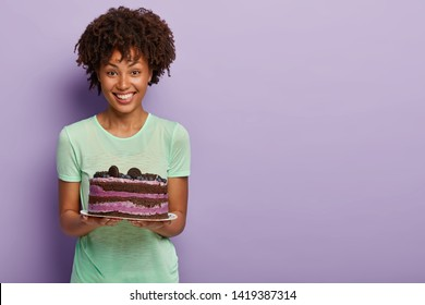 Happy Afro American woman holds delicious birthday cake with blueberry, treats guests with tasty sweet dessert, dressed in casual green t shirt, stands in studio against purple background, free space