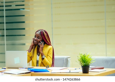 happy, afro american woman in a stylish yellow jacket and multi-colored dreadlocks pigtails workplace in a light large modern office.