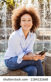 Happy Afro American Young Woman With Glasses Using Smartphone. Outdoor Portrait Of Mixed Race Female, Casual Wear , Looking At The Camera