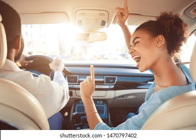 Happy afro couple driving in car and girl singing song, enjoy tavel by auto