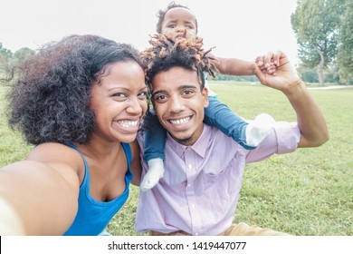 Happy afro family making selfie with smartphone camera - African young parents and their daughter having fun with new trends technology - Love concept - Main focus on mother face