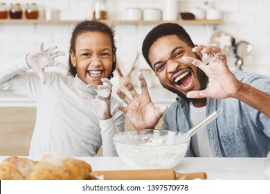 Happy afro father and daughter with funny growling faces, having fun, cooking together at kitchen