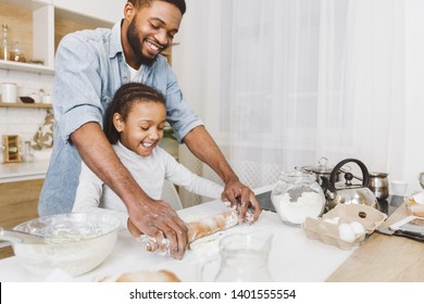 Happy afro man and his child daughter rolling up dough together, having fun. Home bakery concept, copy space