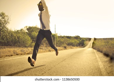 Happy Afro man running on an abandoned road.