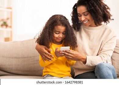 Happy Afro Mother And Daughter Using Mobile Phone Playing Games Together Sitting On Sofa Indoor. Copy Space