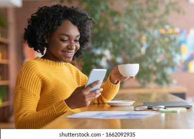 Happy afro woman drinking coffee and using mobile phone at cafe, copy space