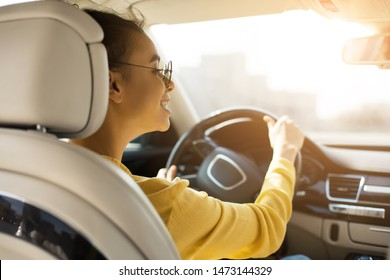 Happy afro woman driving her new car and looking at rear view mirror, free space