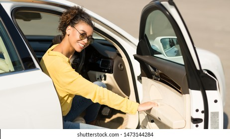 Happy afro woman getting out of car, opening door and smiling to camera