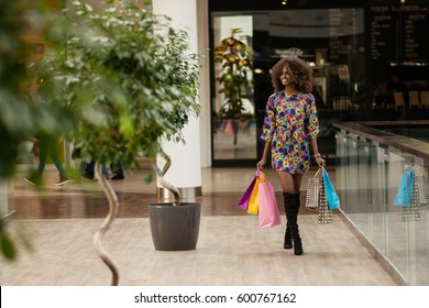 Happy afro woman in a shopping mall carrying coloured bags.