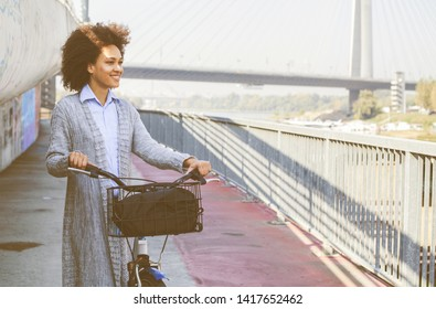 Happy Afro young woman with bicycle enjoy free time on beautiful day at bridge in the city.