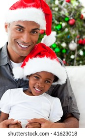 Happy Afro-American dad and daughter wearing a Christmas hat