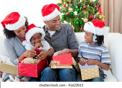 Happy Afro-American family opening Christmas presents at home