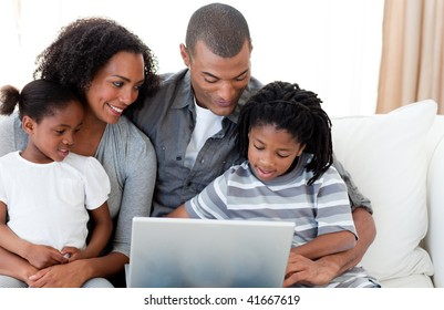 Happy Afro-American family using a laptop on the sofa