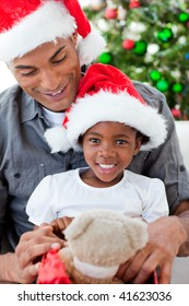 Happy Afro-American father and daughter playing with Christmas gifts
