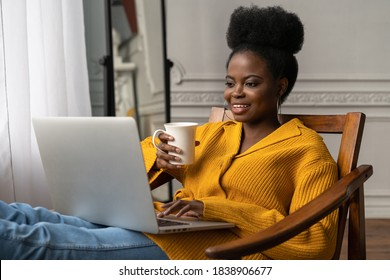 Happy Afro-American millennial woman with afro hairstyle wear yellow cardigan resting, sitting on chair, watching webinar, working online on laptop, talking in video chat, drinking tea or coffee.
