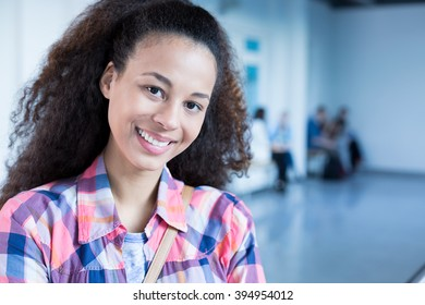Happy, afroamerican student standing at college building