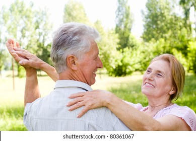 happy aged couple dancing at the nature