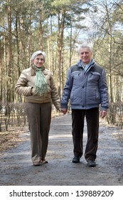 happy aged couple on a walk in the forest in the spring