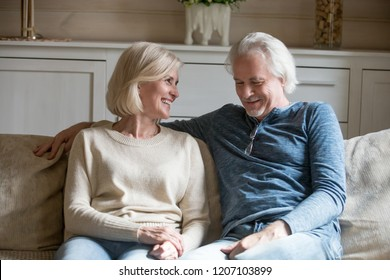 Happy aged couple sit on cozy couch at home talking or having conversation, senior husband and wife enjoy leisure time relaxing on sofa together, smiling elderly man and woman hug and cuddle