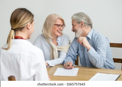 Happy aged couple talking laughing ready to sign document at meeting, senior retired clients buying medical health life insurance, older family make deposit investment in bank with financial advisor