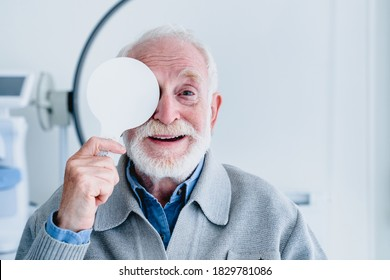 Happy aged grandfather checking up vision closing his eye