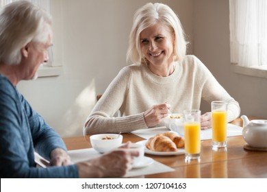 Happy aged husband and wife enjoy breakfast spending time at home together, senior couple eating healthy food smiling talking in morning, laughing elderly man and woman have tasty meal in kitchen