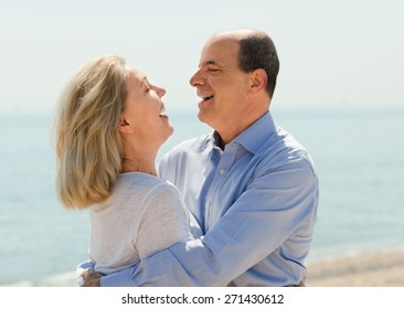 Happy aged lovers laughting outdoor on seaside