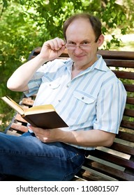 Happy aged man with glasses reading book