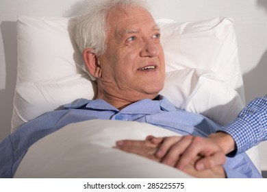 Happy aged man having a guest in hospital