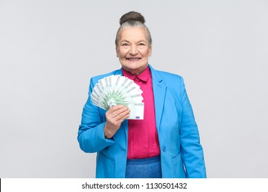 Happy aged woman holding many euro money. Emotion and feelings concept. Portrait of stylish expressive grandmother in light blue suit with collected gray hair. Studio shot, isolated on gray background