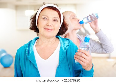 Happy aged woman with plastic bottle of water on background of other female drinking