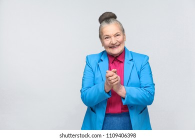 happy aged woman toothy smiling. Emotion and feelings, expressive grandmother with light blue suit and pink shirt standing with collected bun gray hair. Studio shot, isolated on gray background