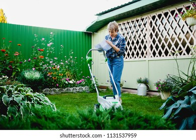 happy age-related woman in jeans and plaid shirt reads the instruction of  lawnmower on green grass in the backyard of a country house on a sunny summer day against the backdrop of a wooden gazebo