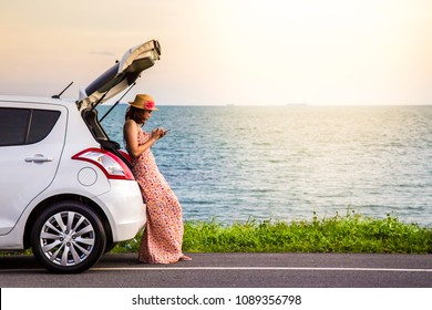 Happy alone young woman traveler on the beach road with white hatchback car with hand holding mobile phone and sea beach background. Traveler car in summer concept