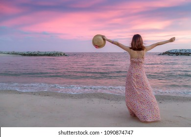 Happy alone young woman traveler hand holding a hat with sunset sea beach background. Traveler in summer concept