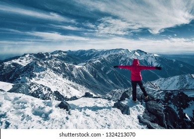 Happy alpinist girl standing at snow covered top of the peak of Jebel Toubkal in Atlas mountains Morocco