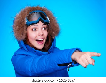happy and amazed skier pointing at something. studio shot over blue background
