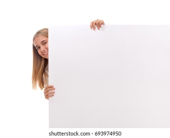 Happy amazed young girl is popping out from the side of white blank banner over white background