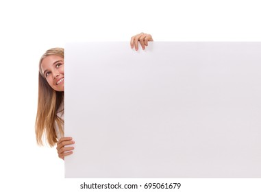 Happy amazed young girl is popping out from the side of white blank banner, looking up over white background