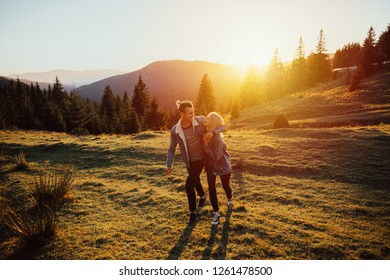 Happy amazing couple hugging at sunset with amazing mountain view.Warm evening sun light.The beautiful young couple enjoying nature at mountain peak.
