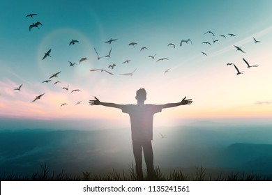 Happy ambitious man rise hand on dawn mountain background. Christian inspire freedom worship praise God on beach  background. One man self confidence open arms enjoying nature the sun good concept
