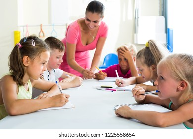 happy american children making writing exercises with help of teacher in class