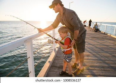 happy American father teaching little young son to be a fisherman, fishing together on sea dock embankment enjoying and learning using the fish rod on a sunny Summer day